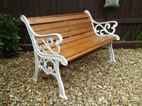 A REFURBISHED GARDEN BENCH WITH VINTAGE CAST IRON ENDS