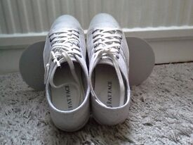 Woman lace up trainers in grey colour.