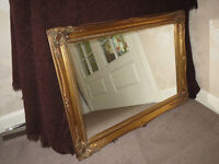 Lovely vintage retro wall mirror, gold frame with ornate detail, clean glass, over table fireplace