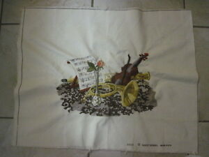 Unframed needlepoint with violin, horn and roses.