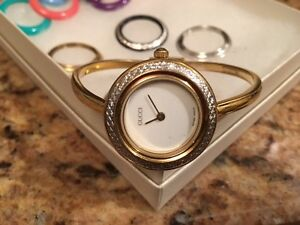 Ladies Gucci bangle with interchangeable bezel plates.