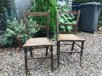 two wooden chairs with cane seating