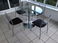 Dining table and chairs, round glass and chrome table with 4 faux leather brown seat chrome chairs