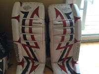 Three pairs of goalie pads and a chest protector