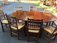 Beautiful Oak Oval Dining room table and 8 matching chairs with wicker seats