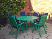 Green painted circular wooden table and 6 chairs complete with cushions.