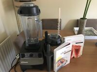 Vitamix Blender with dry goods container and recipe books.