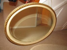 Ornate framed oval gold coloured mirror