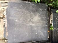 Quantity of used continental slate floor tiles, predominantly black.