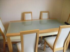 A GLASS TOP TABLE WITH 6 CHAIRS