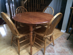 ROUND SOLID WOOD TABLE WITH FOUR WOOD CHAIRS.