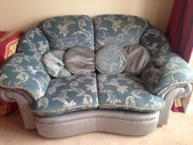 2 seater blue sofa together with matching foot stool and cushions