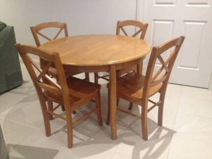 Round timber dining table with four chairs