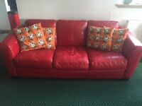 A red leather three seater sofa.