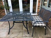 Garden table and 2 seater bench with padded seat. Dark grey weather proof metal in good condition.