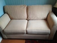 Two seater,cream coloured, sofa bed, excellent condition