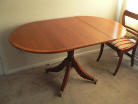 A drop leaf Reproduction Dining Table in Yew with 4 Sabre Leg Chairs