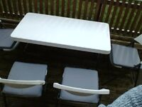 4 foot table and 4 matching chairs with cushions