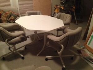 White hexagonal table with 4 upholstered beige swivel chairs