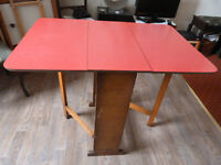 Red melamine top drop leaf kitchen table 77cm high and 61 x 91cm. £20 1 gr 1red wood folding chairs