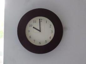 Circular wall clock with dark brown surround