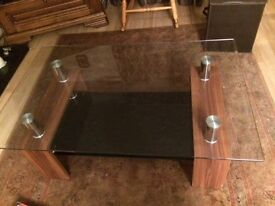 Beautiful glass coffee table with black glass shelf .
