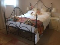 Wrought iron slatted bed with semi orthopaedic mattress.