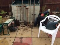 Assortment of garden tools: spades, forks, hoes, stool, chair