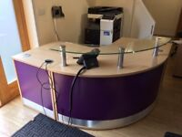 curved reception desk with a glass top + wood filing cabinet
