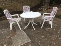 White plastic table and chairs set with parasol