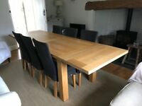 Oak Table, 6 chairs aged leather seats. 1.8m by 0.9m. Two 0.45m extensions. Linen chair covers.