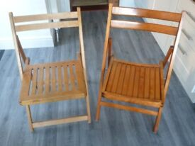 Pair of solidly built folding wooden chairs.