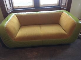 Lovely comfy, compact sofa with retro curved shape, leather edges with fabric seat