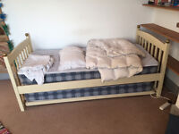 Pair of white wooden single beds each with roll-under spare bed on wheeled frame.