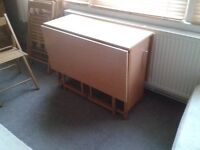 Dropleaf table and 4 chairs which fit inside table when not in use. As new condition.