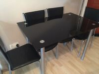 Black glass dinning table and 4 chairs