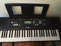 Yamaha Keyboard EZ220 with stand. lighting keys, and music book.