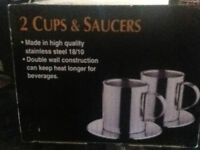 FOUR BRAND NEW STAINLESS STEEL MUGS and SAUCERS IN ORIGINAL BOX