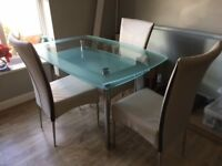 glass dining table & three cream faux leather chairs