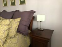 Two bedside table lamps, with white shades