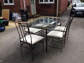 Dining table & 6 matching padded cream chairs. Glass table top & cast iron frame