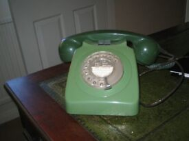 Old fashioned green telephone with dialling holes