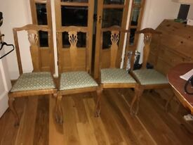 4 high back dining chairs with green/cream printed upholstered seats.