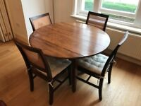 "Dining Table, Rond 120cm with foldable ""ears"". Height 79cm. Incl 4 wooden chairs. Good condition!"