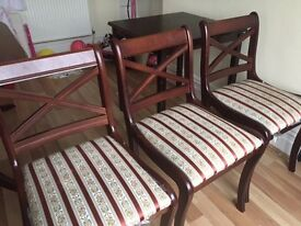 Three solid wood upholstered chairs.
