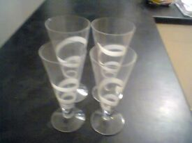A lovely set of Dartington glass flutes with a white pattern with co-ordinating set of bowls.