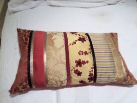 6 pretty cushions in pinks, reds, yellows and gold