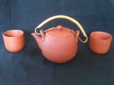 CANE HANDLED TERRACOTTA POTTERY TEAPOT + TWO TERRCOTTA POTTERY CUPS