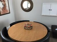 Round solid royal,oak table & 4 black leather chairs
