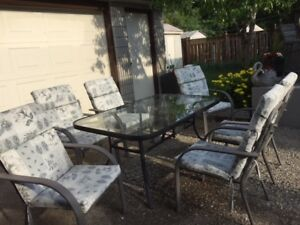 Patio set with glass table and 6 padded chairs